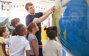 Teacher shows kids giant globe