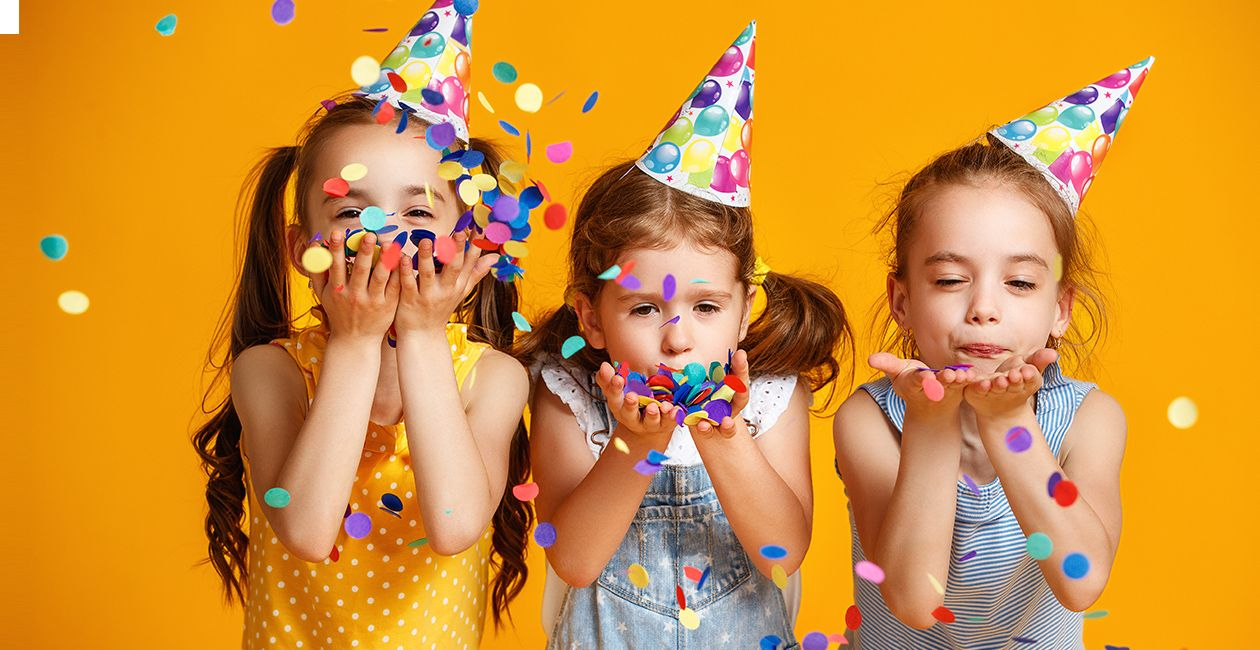 3 girls wearing birthday hats celebrating a birthday with confetti on yellow background
