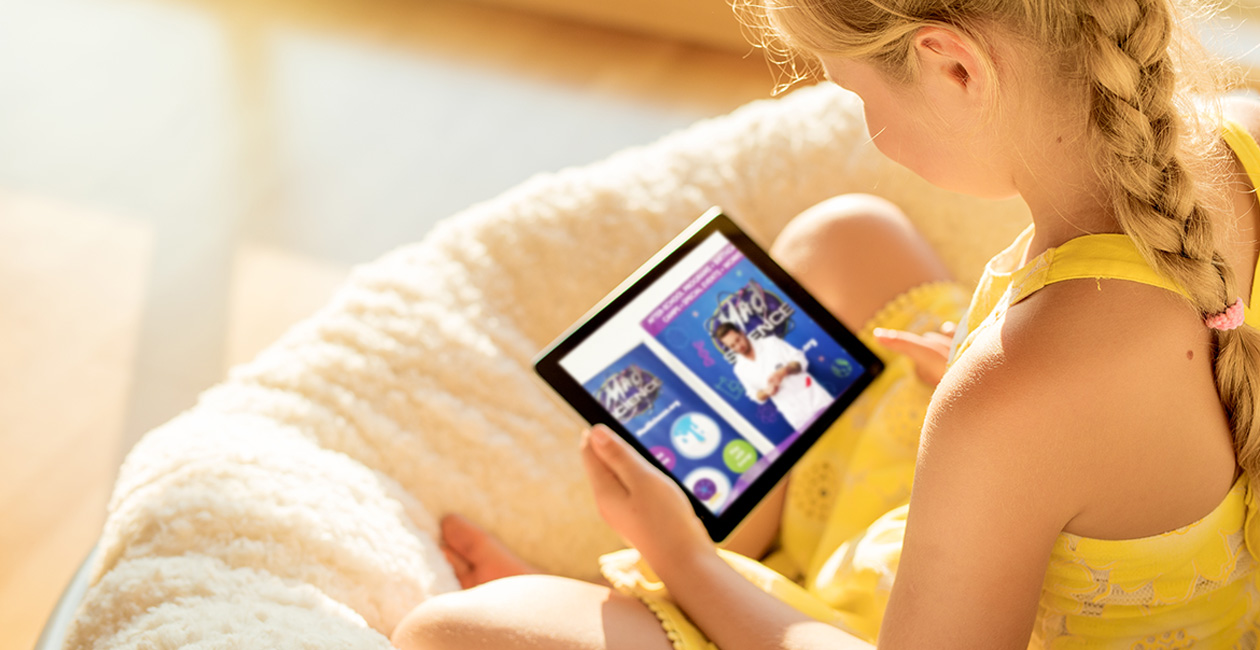 Girl sitting holding an ipad while watching a mad science virtual learning class