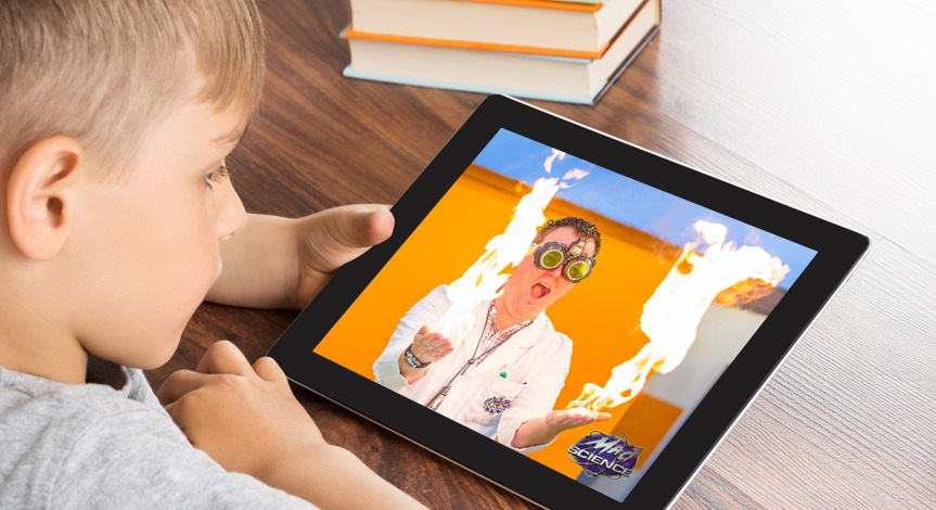 Boy looking at ipad with a mad science instructor on the screen performing with fire on both hands.